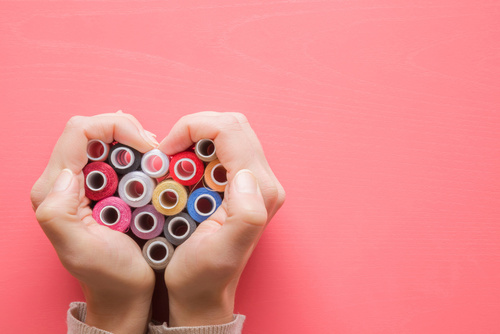 Colorful spools of threads in hands heart shape on the pastel pi