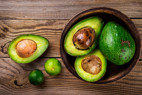 Avocado and lime on rustic wooden table. Healthy food concept. T