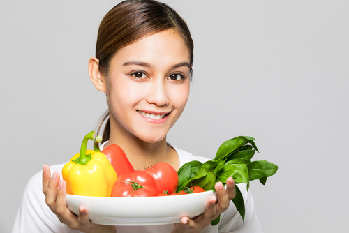 Young woman holding vegetables.